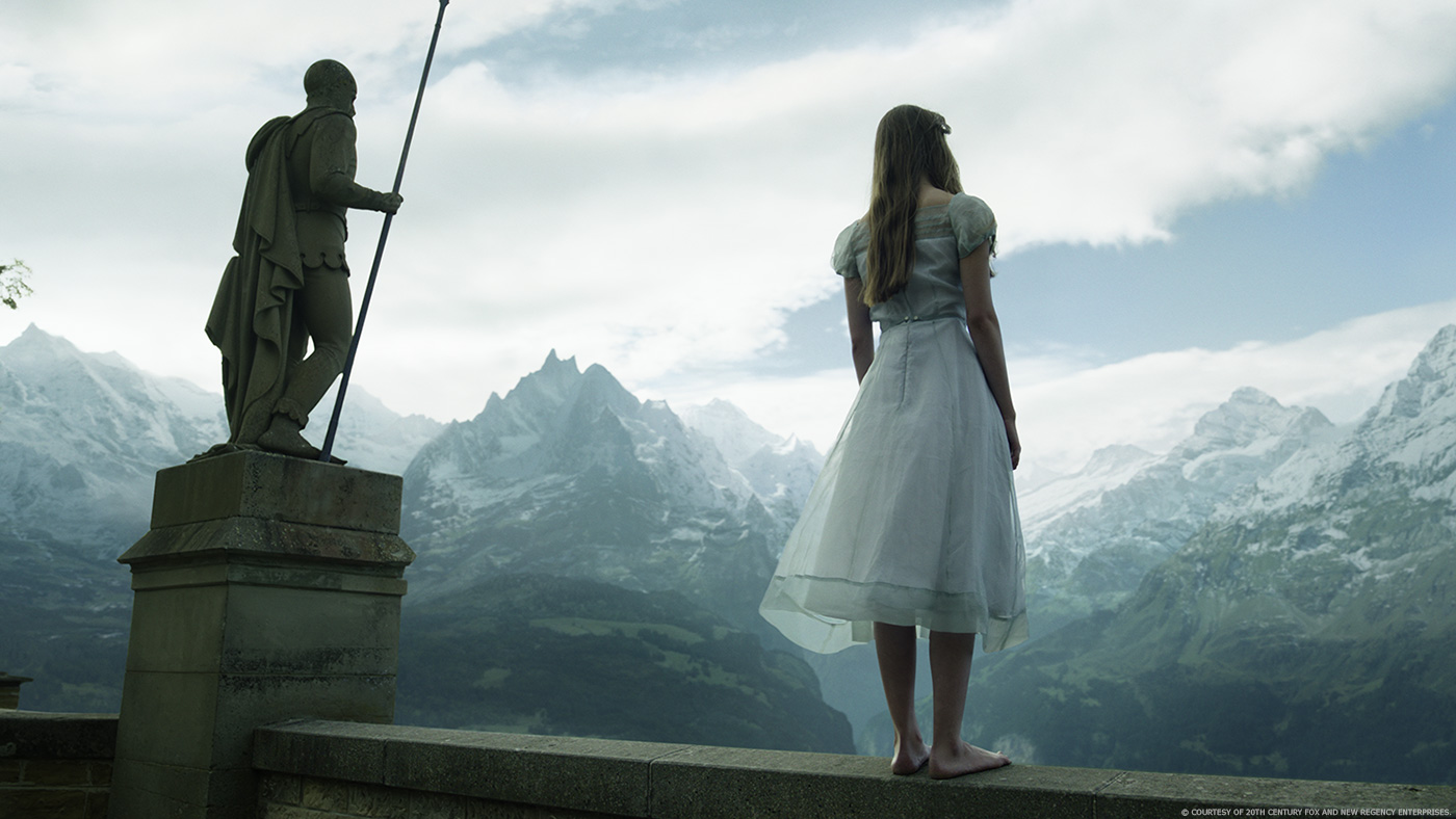 A cure for Wellness woman on ledge in front of mountains